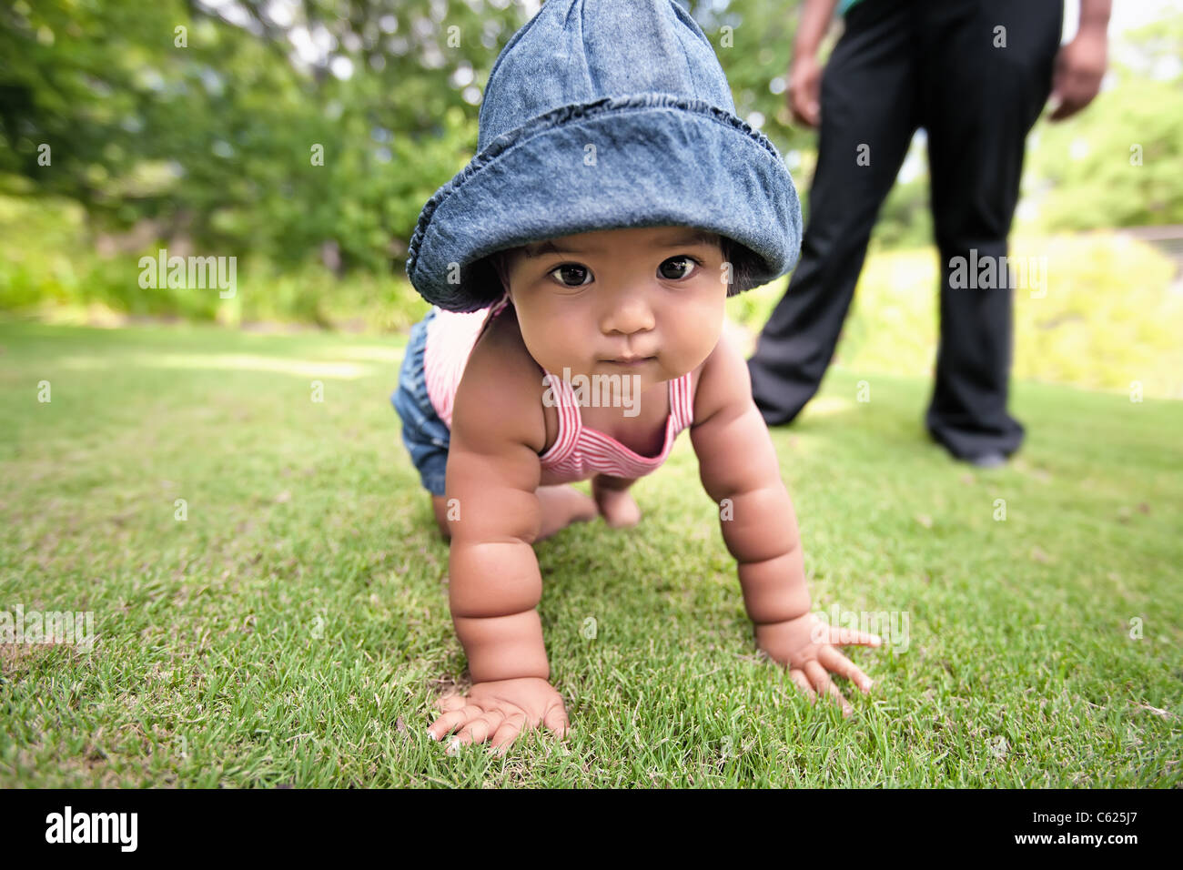 Baby girl crawling on grass, wearing a denim hat, with parent in background observing her chubby arms support her - Stock Image