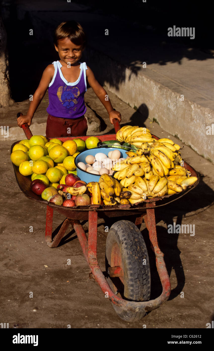small smiling mexican boy with a whellbarrow ful of fruits for sale. Sweet Stock Photo