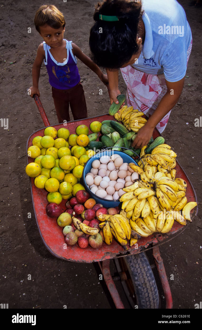 small mexican boy with a whellbarrow ful of fruits and eggs for sale. Buyer inspecting the goods - Stock Image
