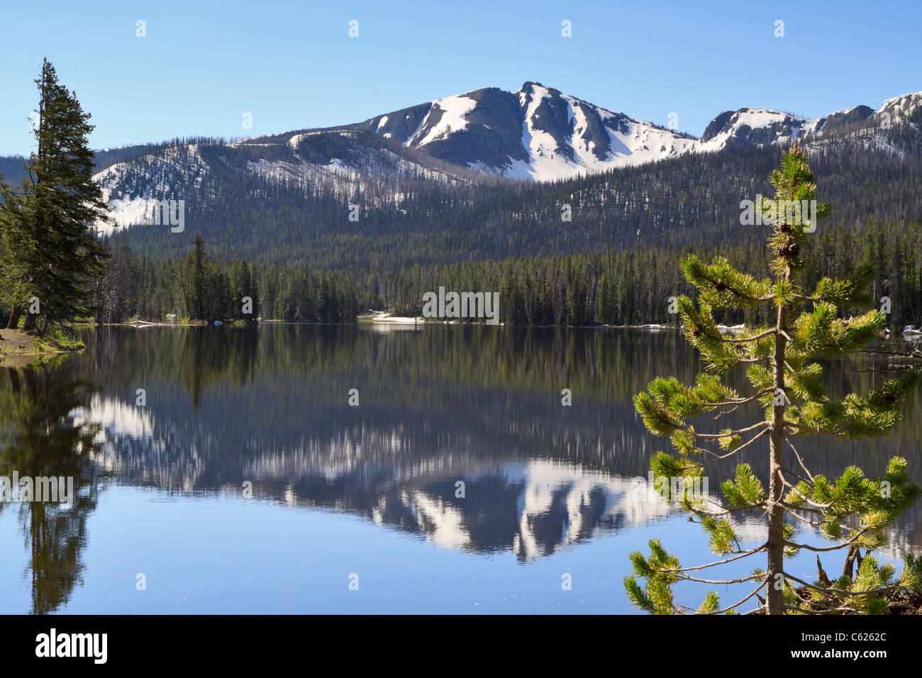 Sylvan Lake, Yellowstone National Park, Wyoming. Snow covered mountains reflected in still water near Sylvan Pass. Stock Photo