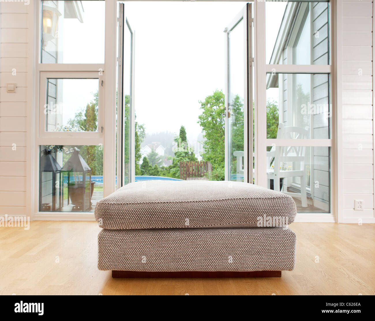 A large chair cushion in front of a large open window - Stock Image