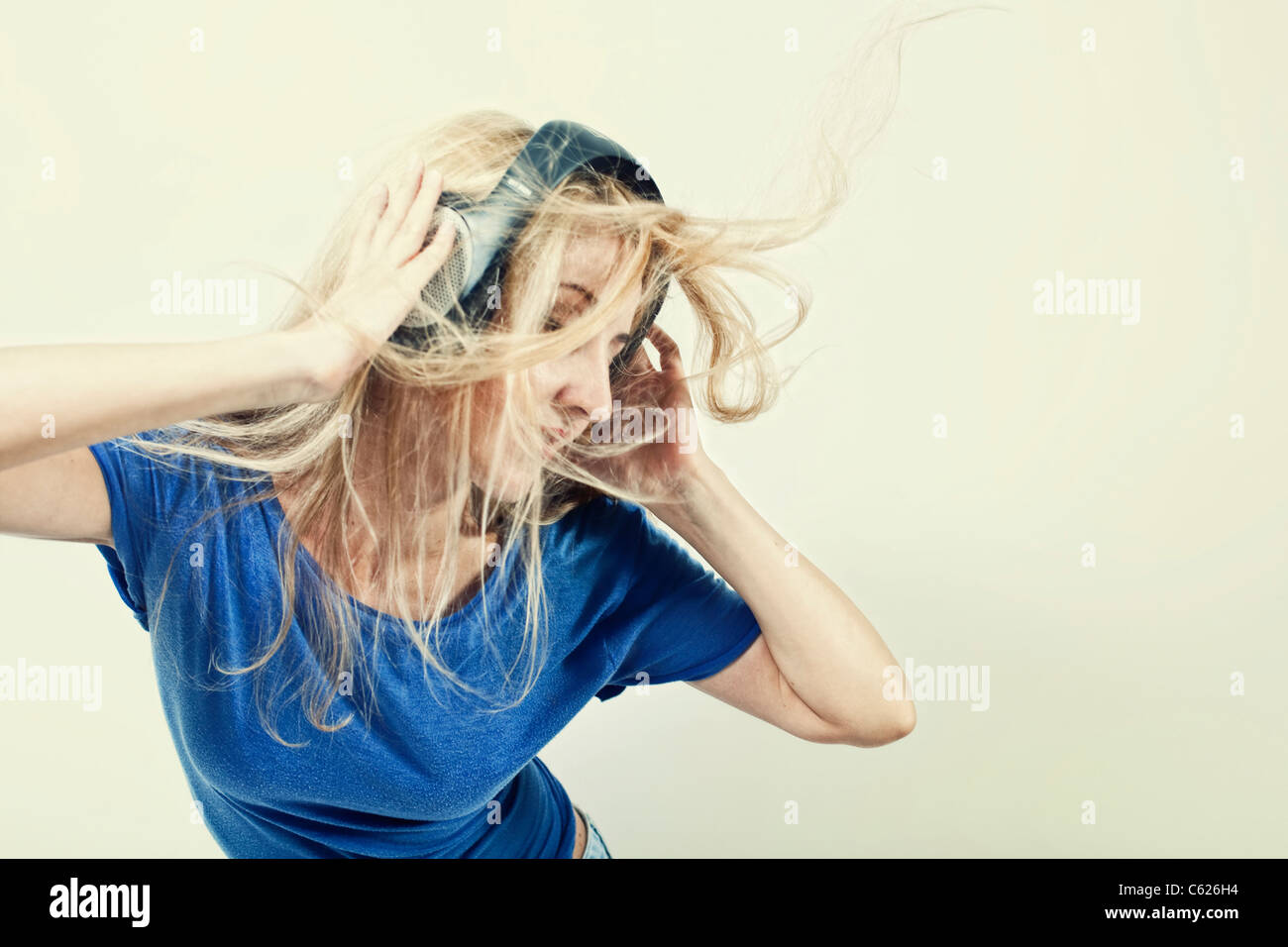 young woman singing with headphones on a light background Stock Photo