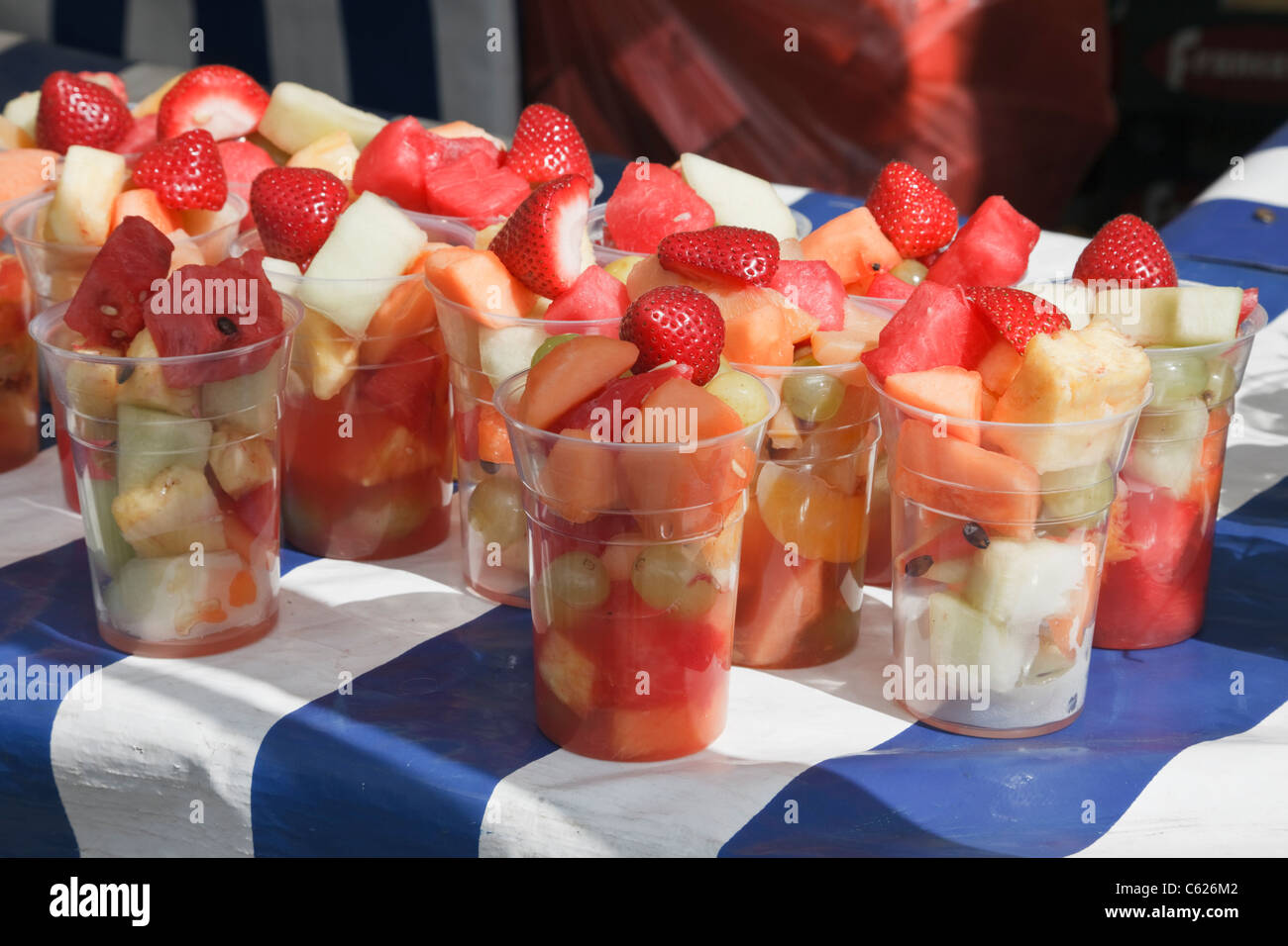 Mixed fresh fruit cocktails for sale in disposable plastic cups on a market stall with blue and white tablecloth - Stock Image