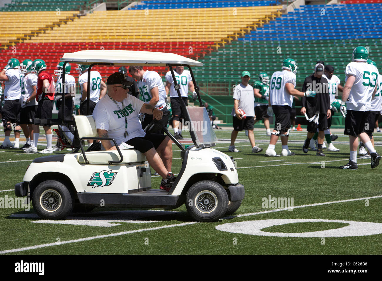 coaching staff drive golf cart on the pitch during saskatchewan roughriders pre season training mosaic stadium taylor - Stock Image