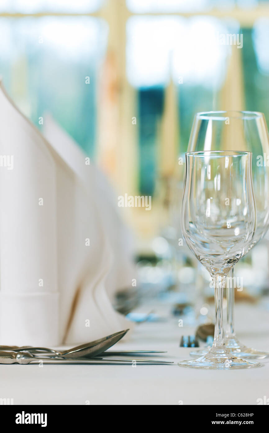 Wedding - feastfully decorated table with silverware and glasses - Stock Image