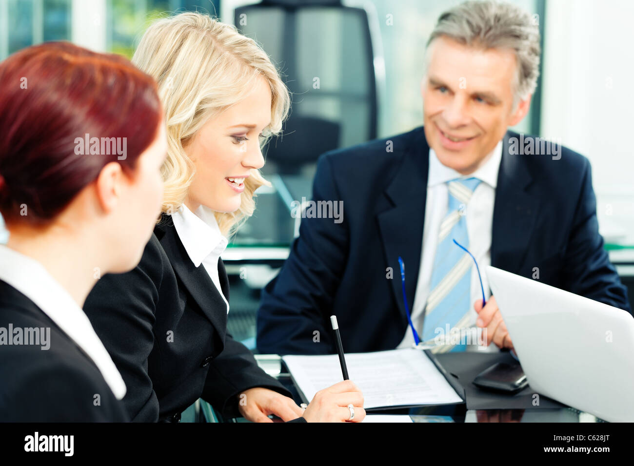 Business - meeting in an office; the businesspeople are discussing a document - Stock Image