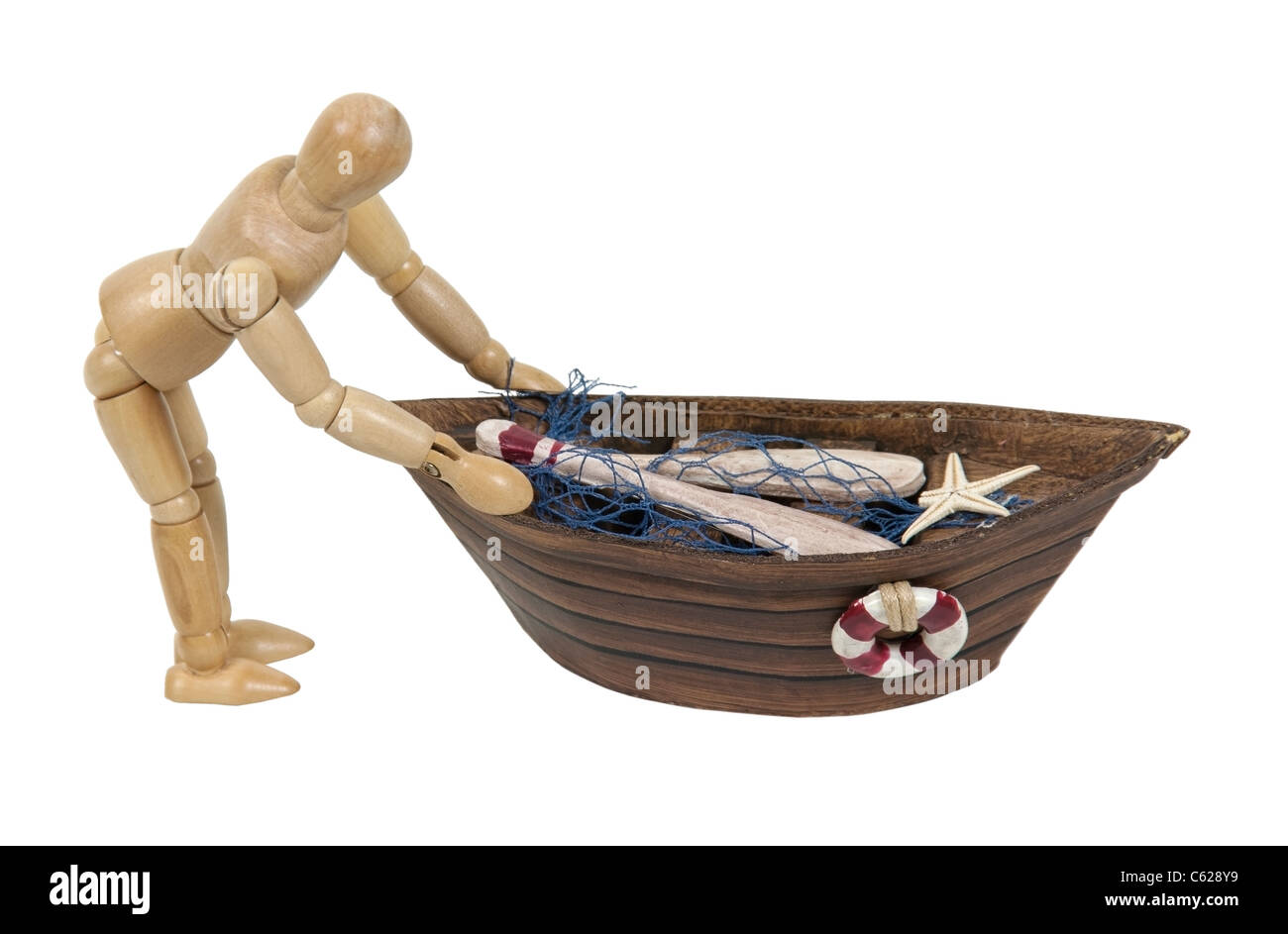 Wooden model representing a person pushing out a row boat with nets - path included - Stock Image