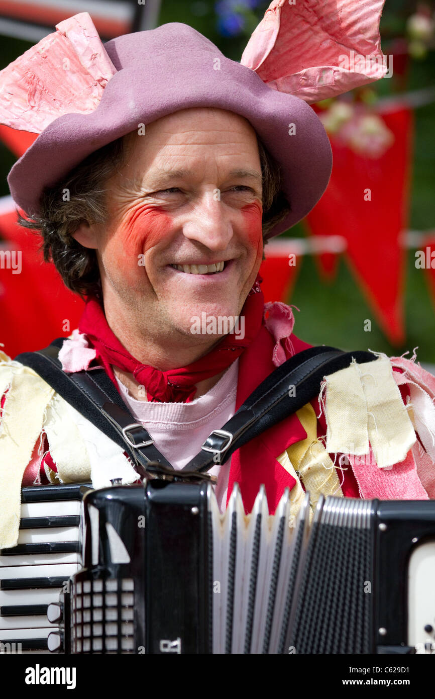 Man dressed in pink, fancy dress, a 'Fell bred Farmer' at the Cumbrian Unfair Games at the Lake District - Stock Image