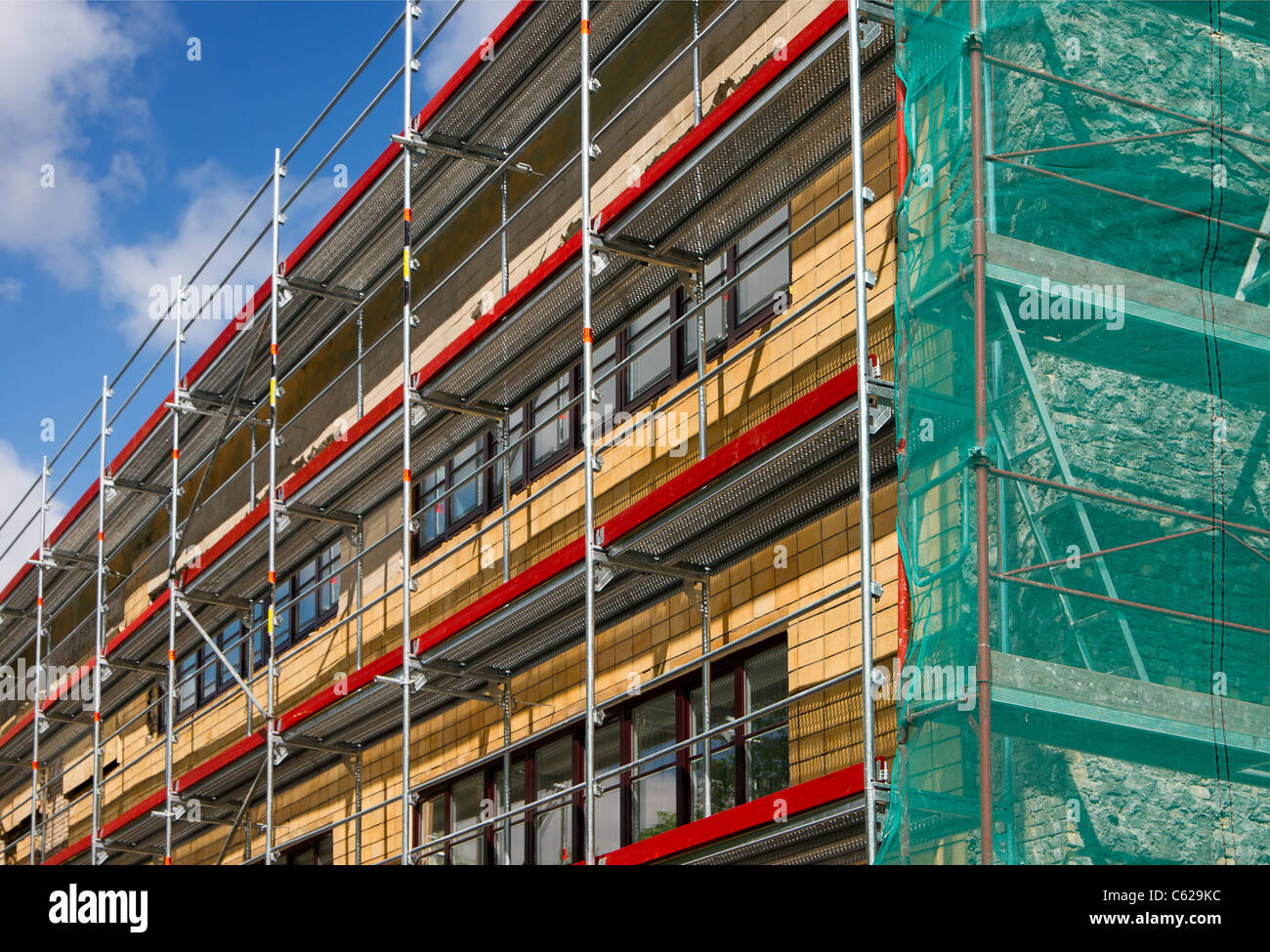 Corner view of a building with scaffolding enclosed in green safety fabric - Stock Image