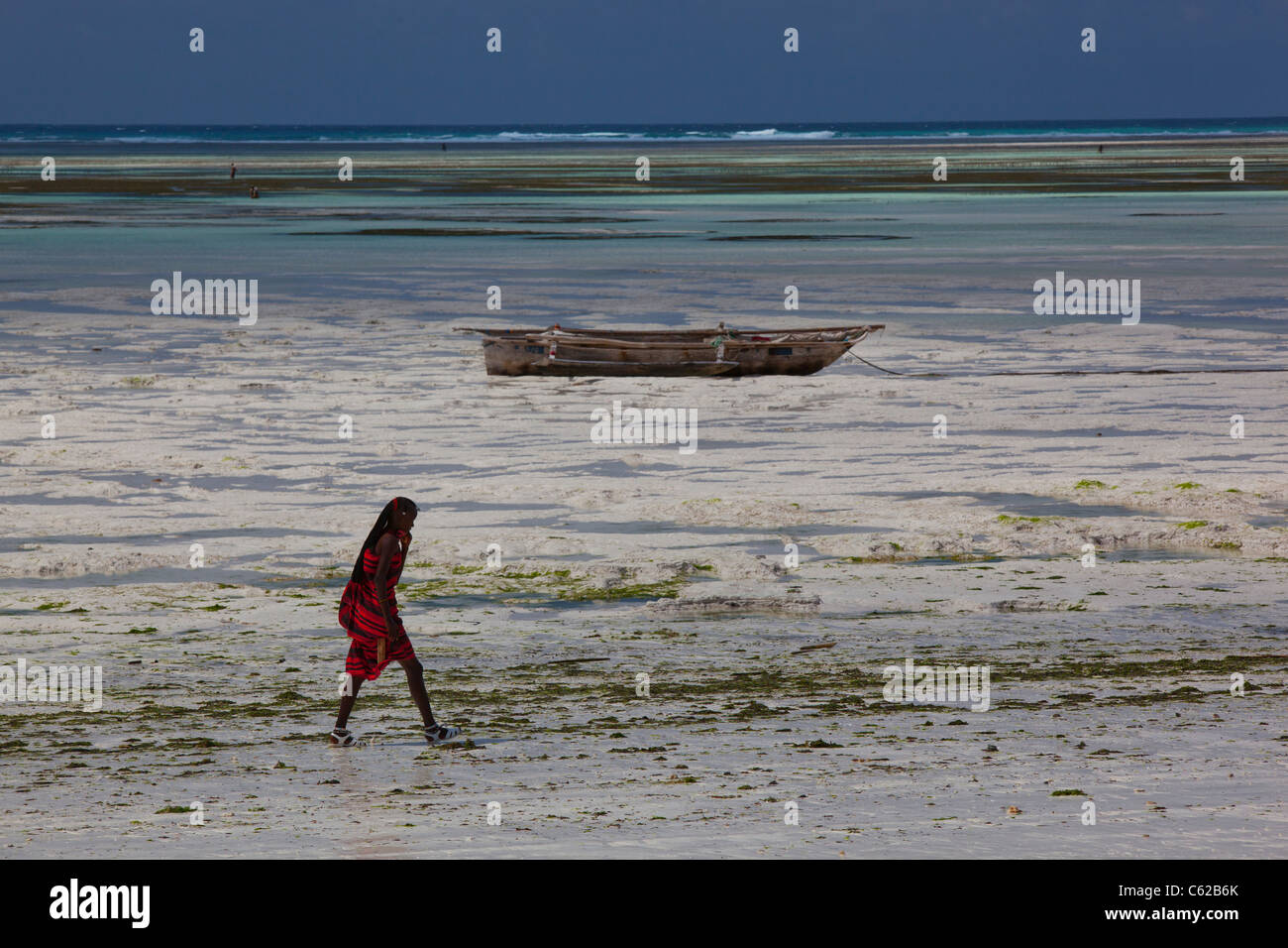 A man dressed in traditional Masai clothes walking on the beach in Zanzibar, Tansania. - Stock Image