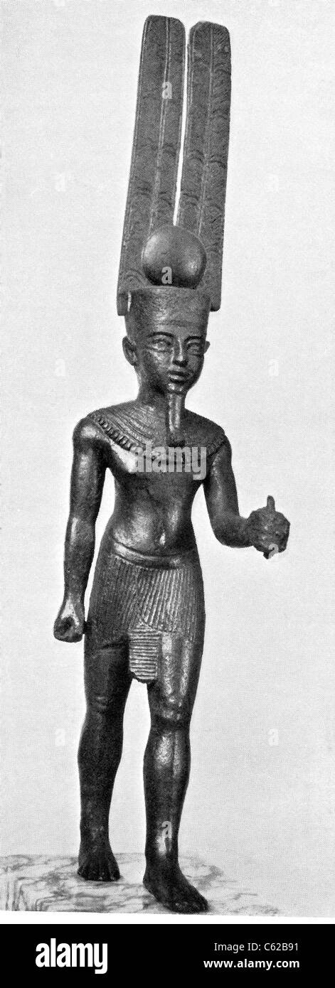 This ancient Egyptian statue depicts the god Amun Re wearing the solar disk with two tall plumes. - Stock Image
