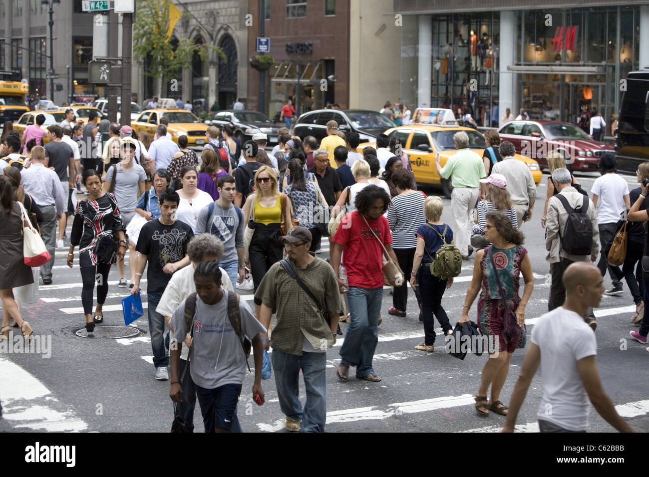 The street is always crowded with tourists, New Yorkers and workers at 5th Avenue and 42nd Street in New York City. - Stock Image