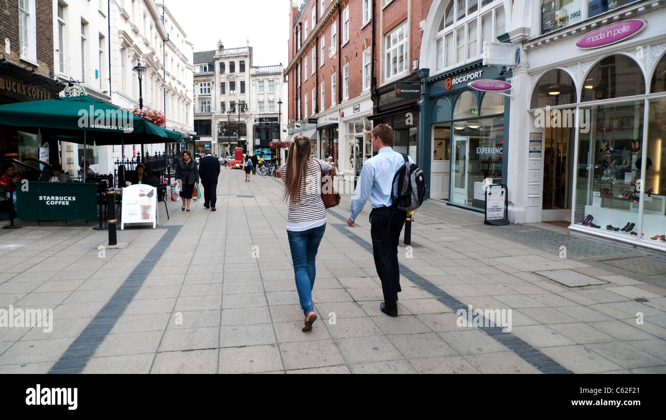 A young couple viewed from behind walking along past shops and boutiques on New Bond Street in London W1 England - Stock Image