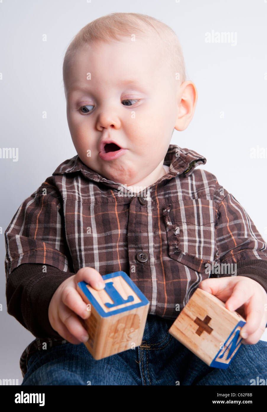 Nine month old baby boy playing with learning blocks. - Stock Image