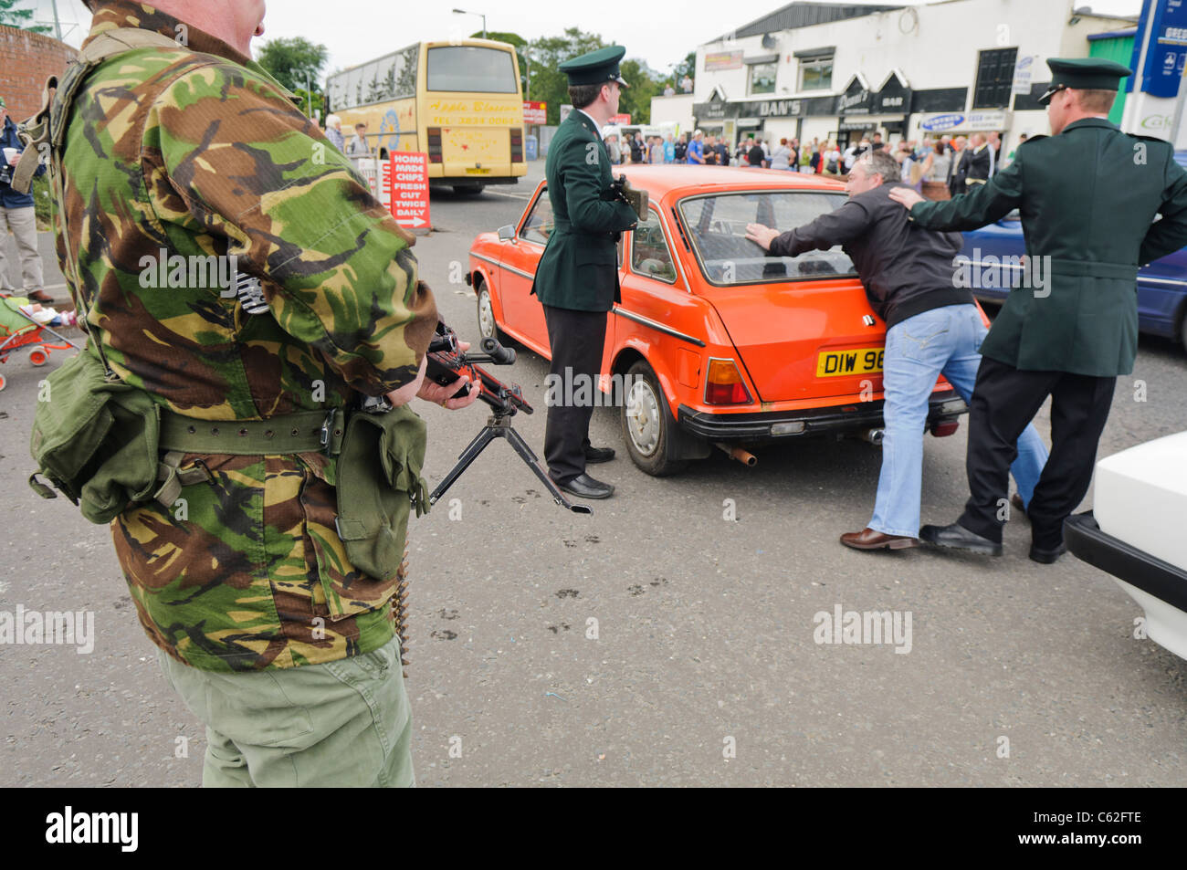 Men dressed in RUC and Army uniforms reenact a stop and search in Northern Ireland in the 1980s - Stock Image
