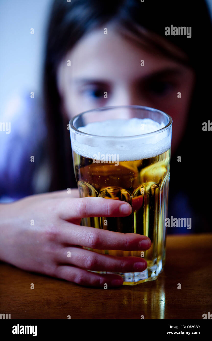 An underage child drinking alcohol. - Stock Image