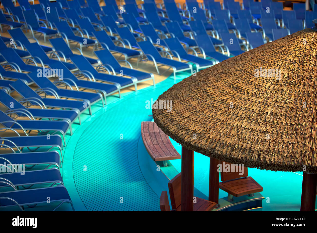 Cruise Ship Lounge Chairs, Swimming Pool And Grass Covered Cabana At Night  With No Passengers. European Vacation.