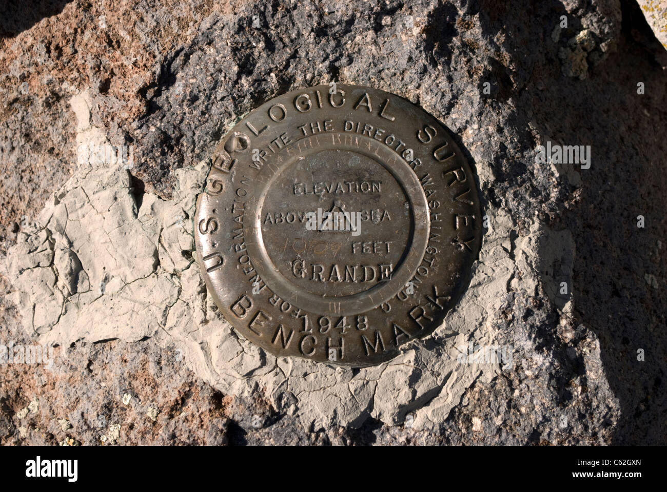 A Bench Mark marker found at the peak of Cerro Grande, identifying the official summit, elevation, and date of survey. - Stock Image