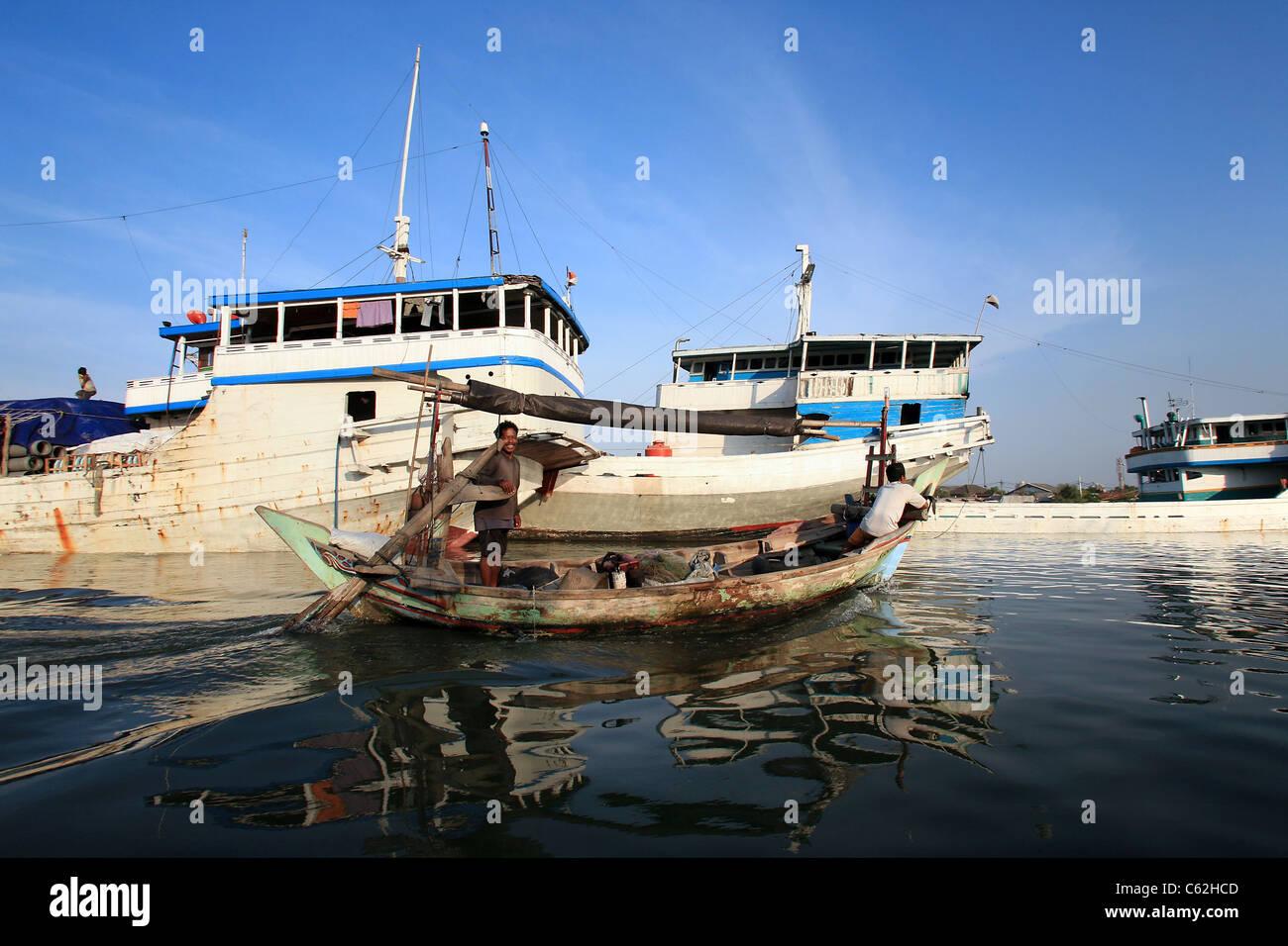 Fishermen motor past wooden schooners in Sunda Kelapa in Jakarta, historically known as Batavia. Jakarta, Java, - Stock Image