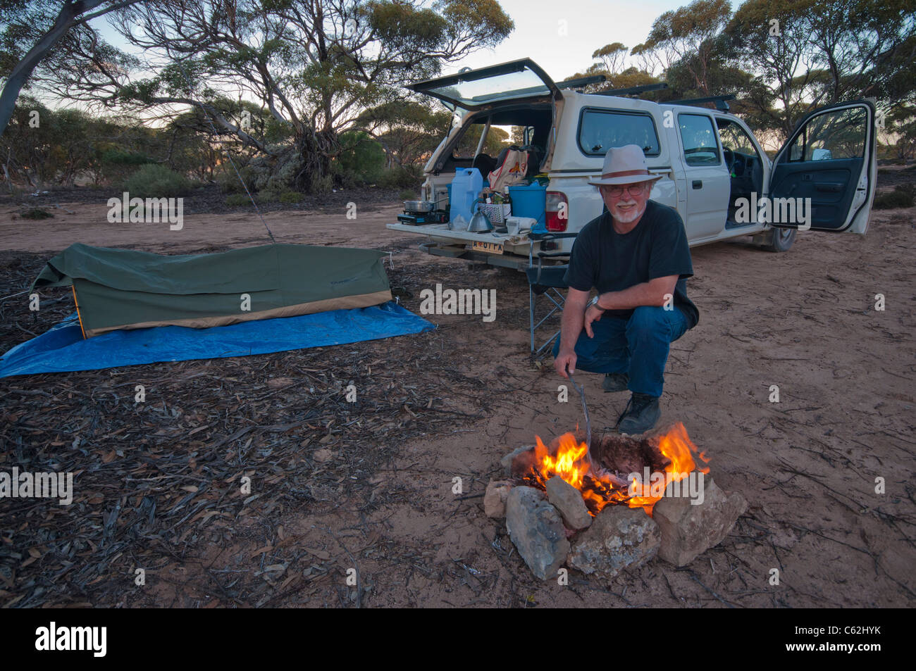 Man with campfire and pitched swag in the Australian outback - Stock Image