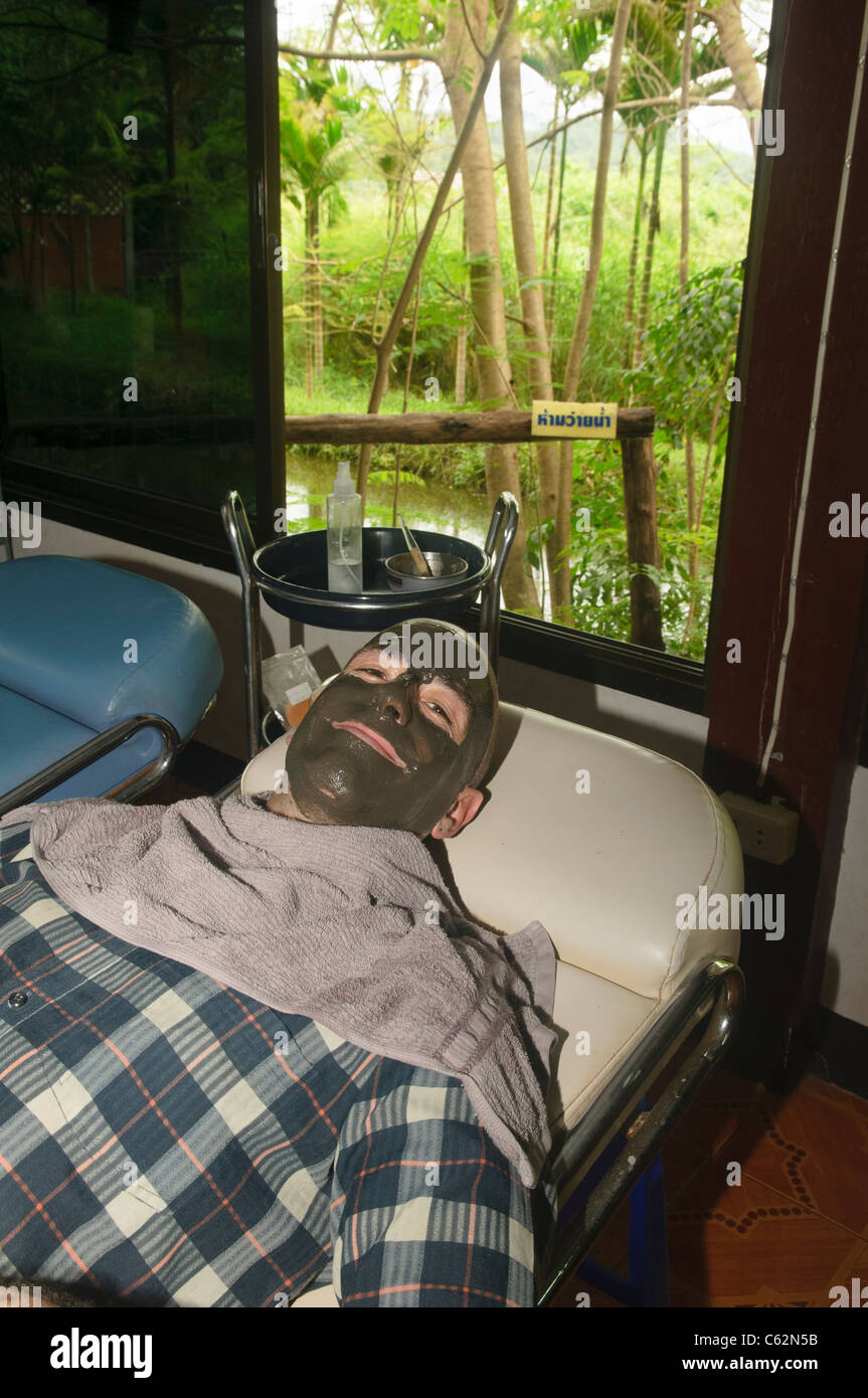 tourist enjoying a therapeutic mud treatment at the Phu Klon Mud Spa in Mae Hong Son, Thailand - Stock Image