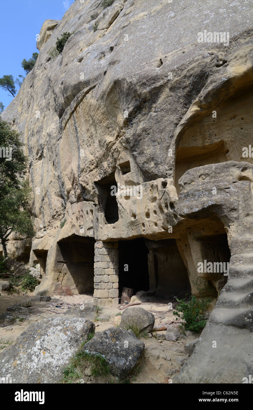 Troglodyte Houses or Cave Dwellings Cut Out of the Cliff Face at Calès, Lamanon, Provence, France - Stock Image