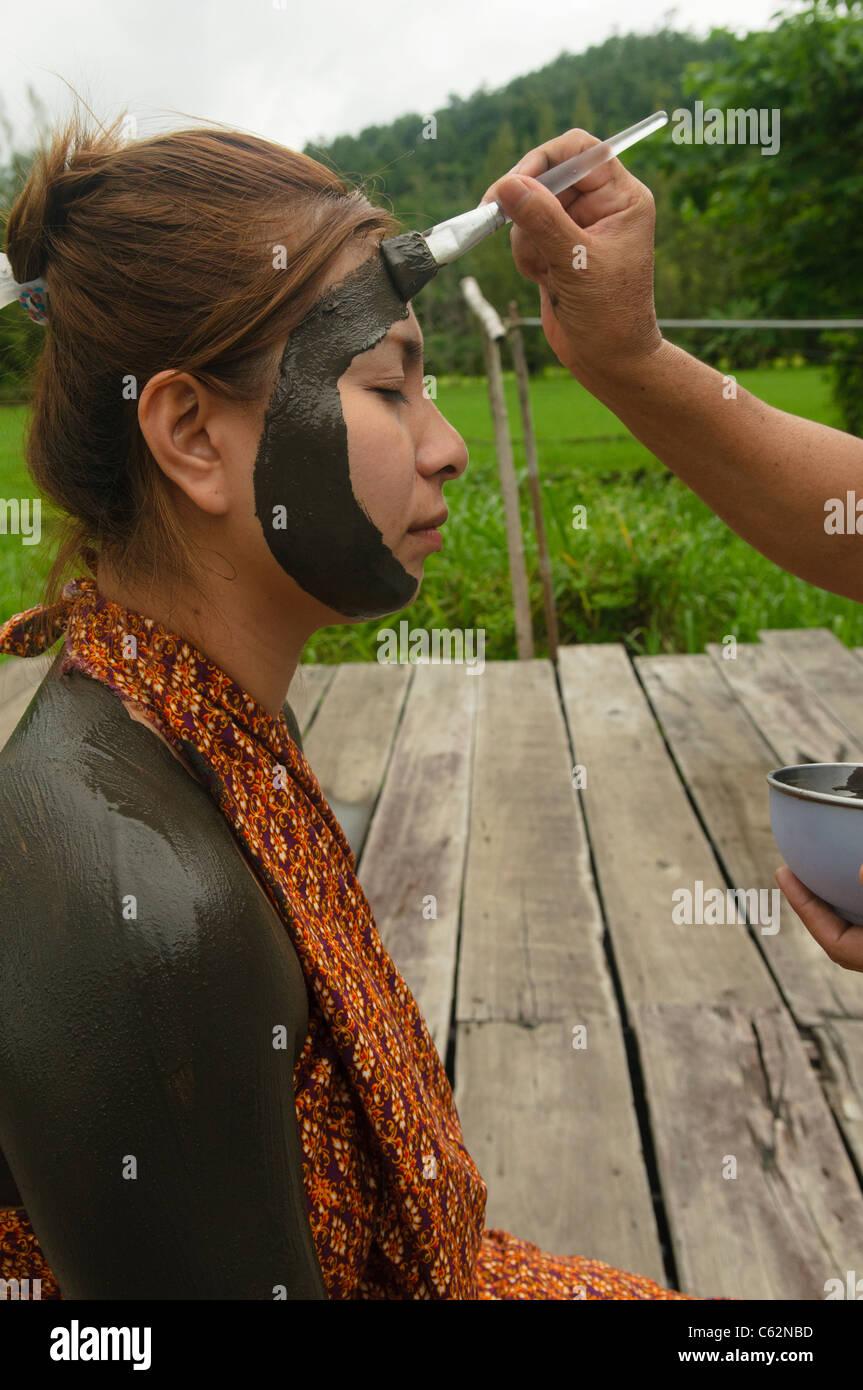 Thai woman enjoying a therapeutic mud treatment at the Phu Klon Mud Spa in Mae Hong Son, Thailand - Stock Image