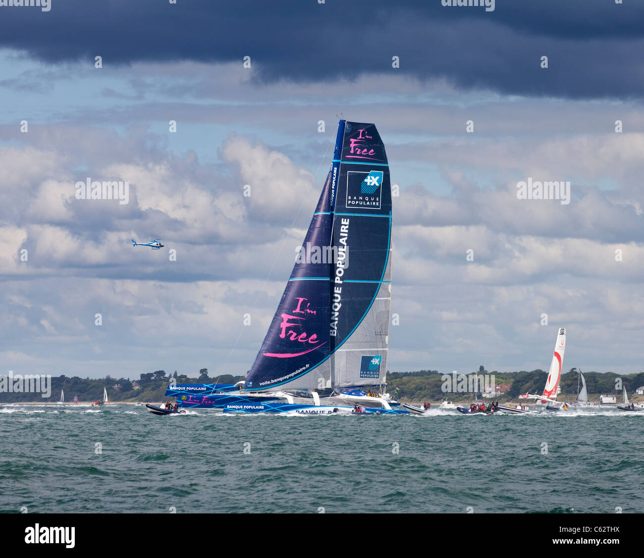Maxi Banque Populaire V sail racing trimaran skippered by Loick Peyron high tech modern performance fast carbon - Stock Image