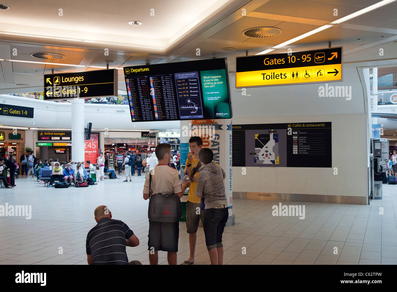 Flight Departures Board Gatwick Airport South Terminal UK electronic holiday destinations holidaymakers waiting - Stock Image