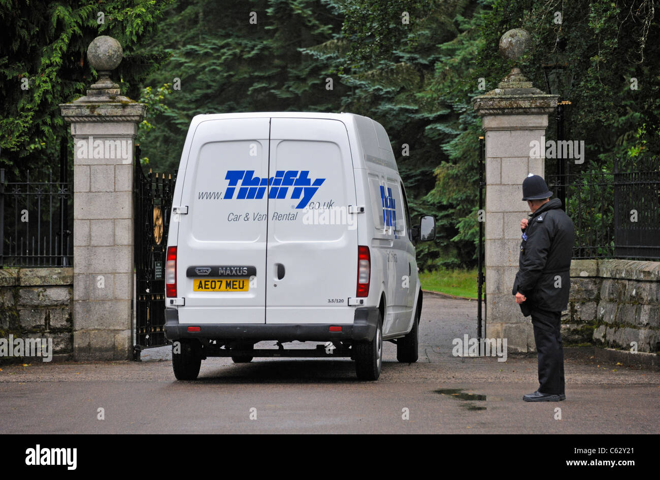 Policeman directing Thrifty Car and Van Rental van at gates to Balmoral Castle. Balmoral, Royal Deeside, Aberdeenshire, - Stock Image