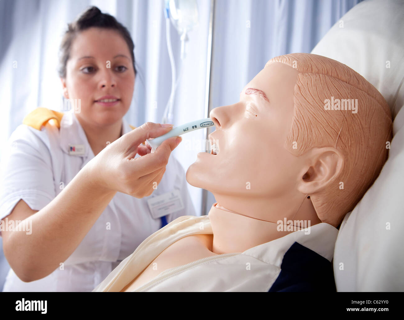 A trainee nurse using a lifelike mannequin during her hospital training. - Stock Image