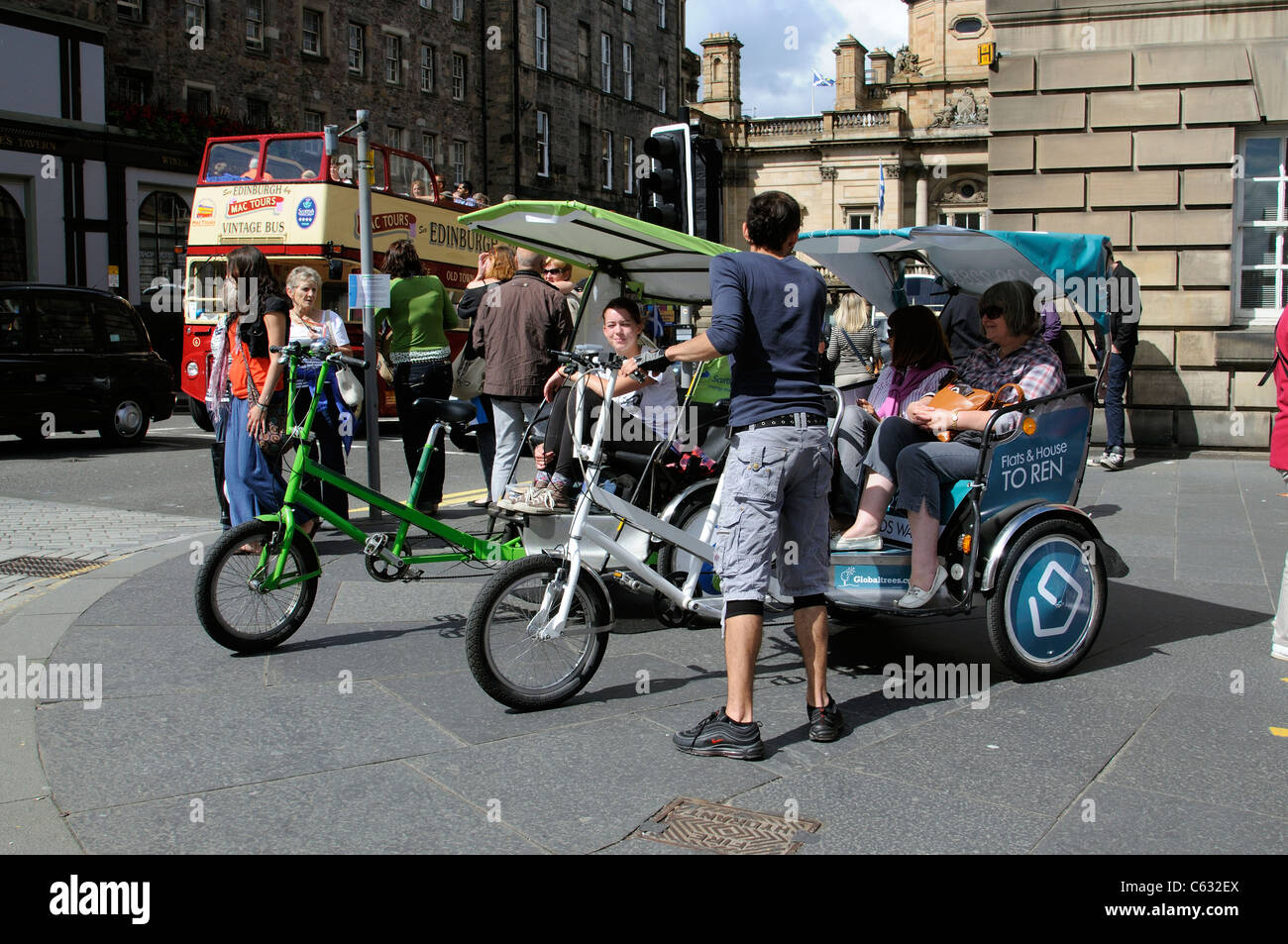 Cycle taxis for hire on a street corner in Edinburgh Scotland UK - Stock Image