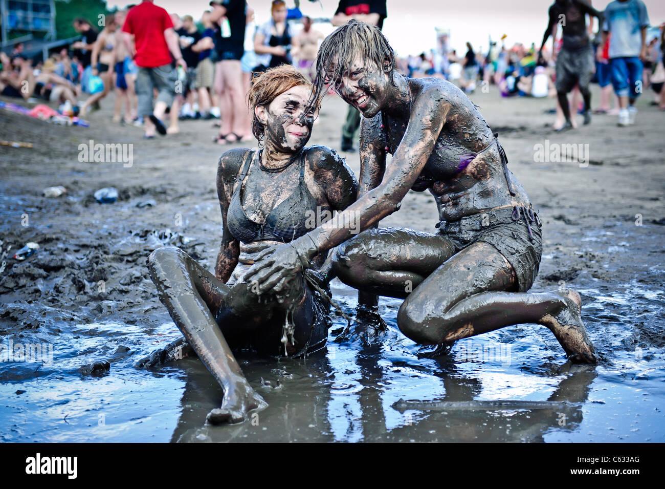 Young women having fun in the mud at the Przystanek Woodstock - Europe's largest open air festival in Kostrzyn, - Stock Image