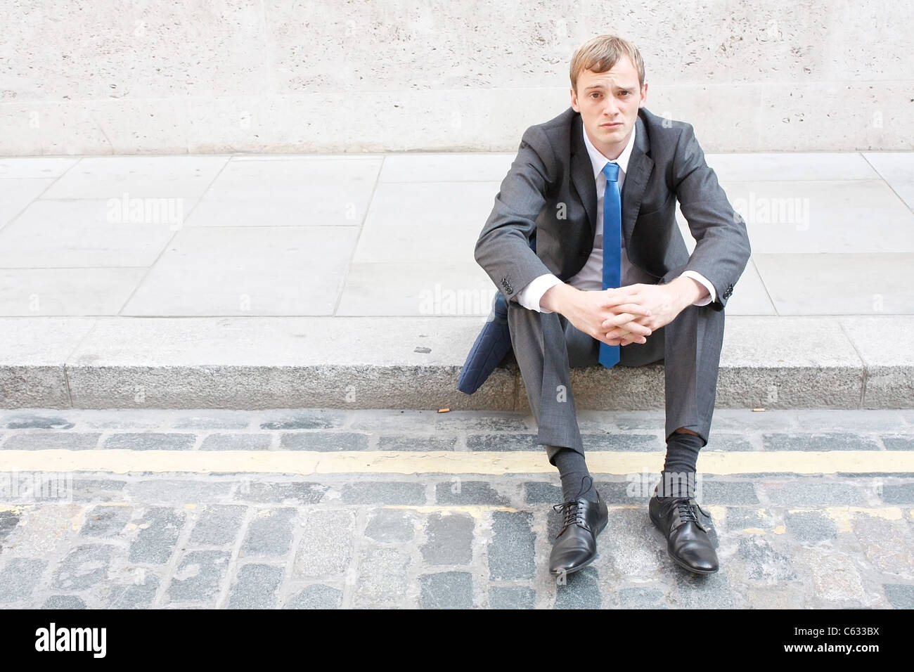 A worried business man sitting on some stairs - Stock Image