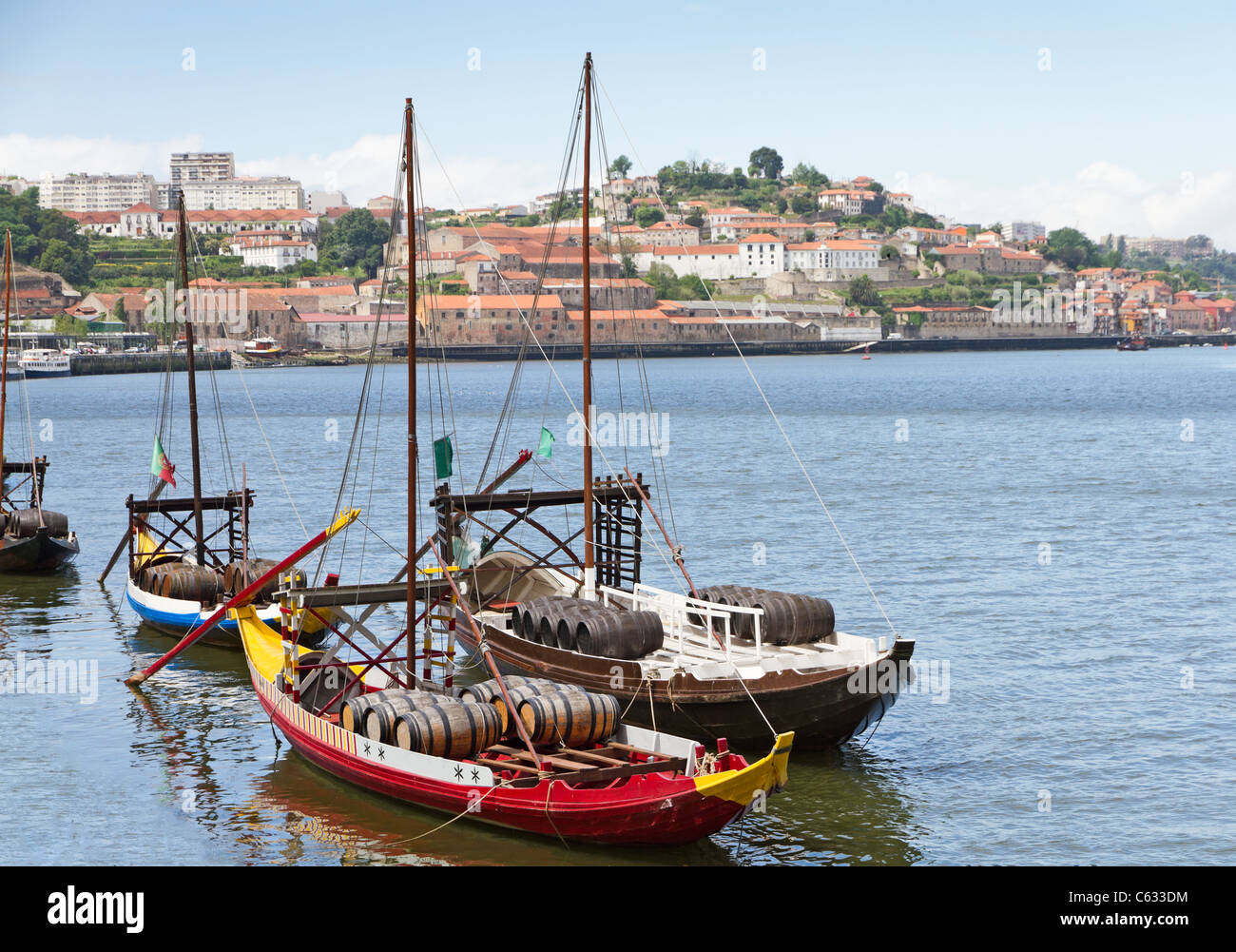 Port wine storage warehouses and transport boats at river Duoro in Vila Nova de Gaia opposite Porto, Portugal Stock Photo