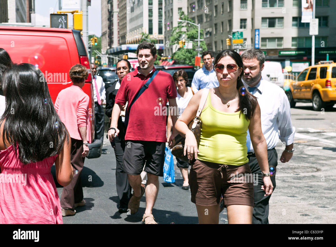diverse crowd pedestrians dressed for a hot summer day cross 57th street at Sixth Avenue in Midtown Manhattan New - Stock Image