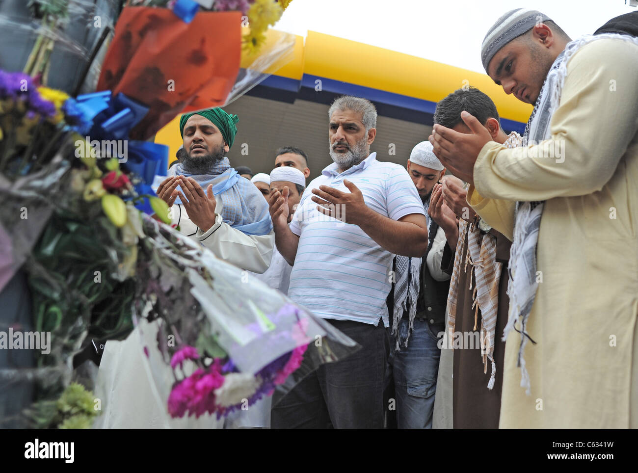 Grieving father Tariq Jahan (centre) praying near a memorial where his 21 yo son was killed during the 2011 riots - Stock Image