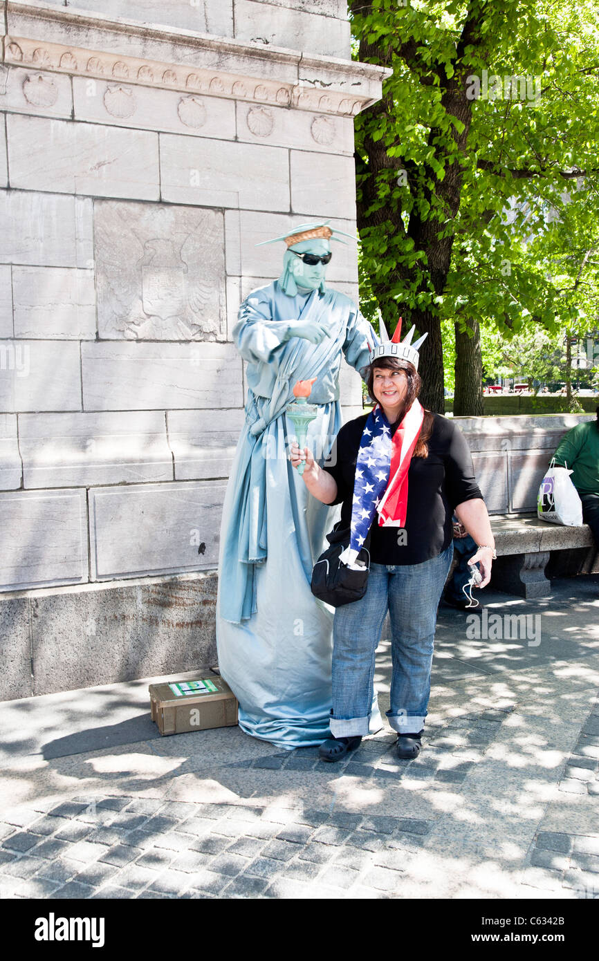 woman tourist wears crown & holds torch aloft smiling saucily as she poses next to mime dressed as Statue of - Stock Image