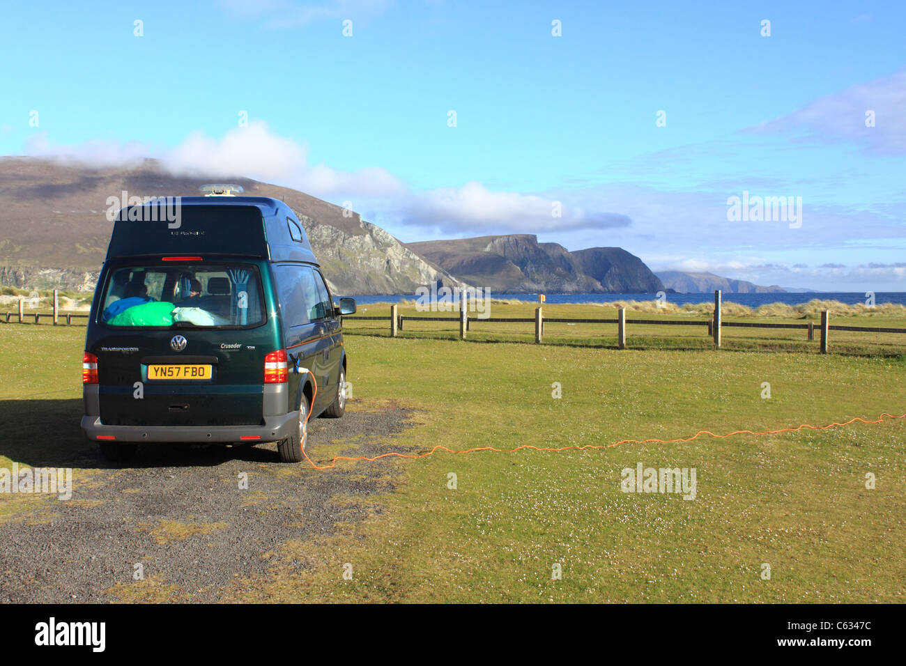 VW campervan at a campsite in Keel, Achill Island, Ireland, with the Minaun cliffs in the distance - Stock Image