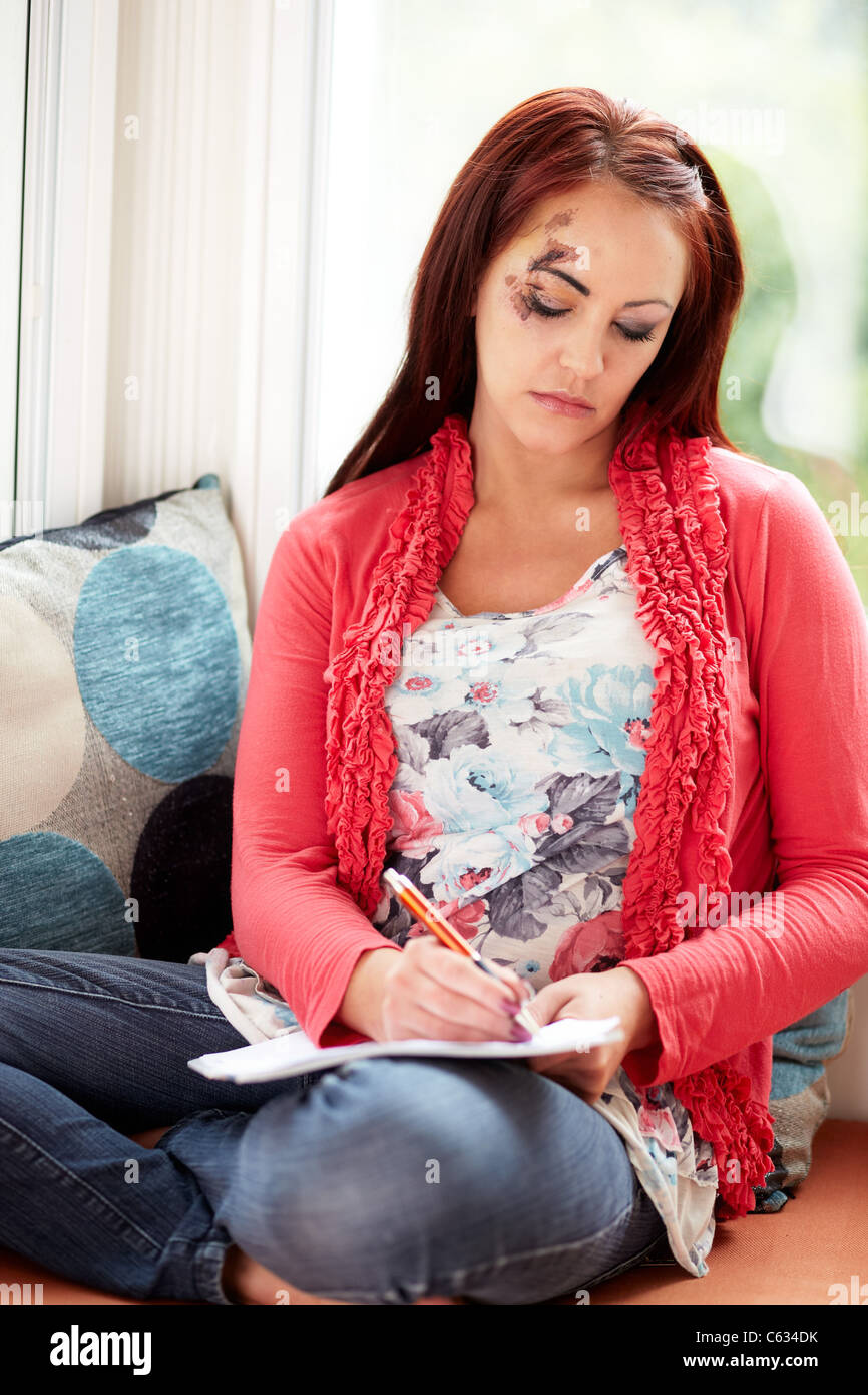 Woman filling out injury claim form - Stock Image