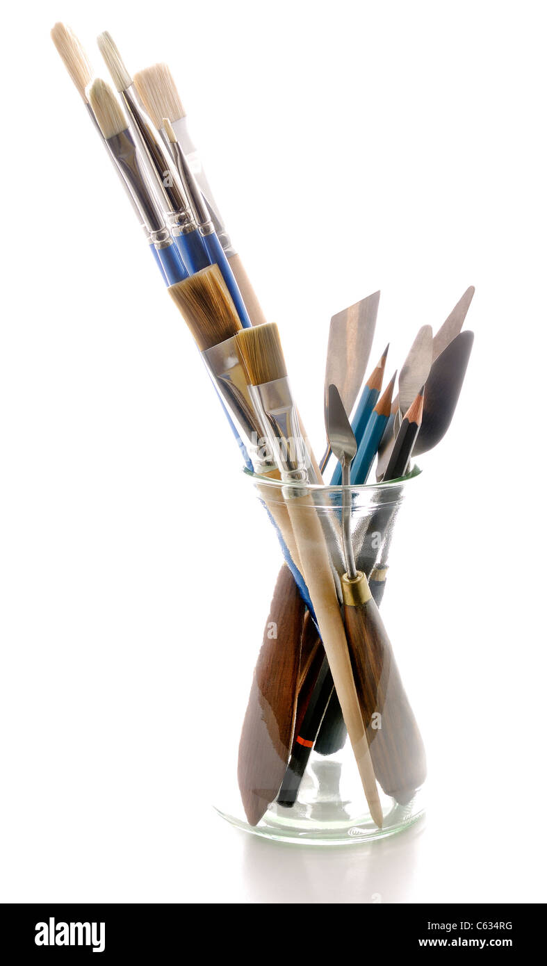 artists brushes pencils and pallette knives in a glass jar - Stock Image