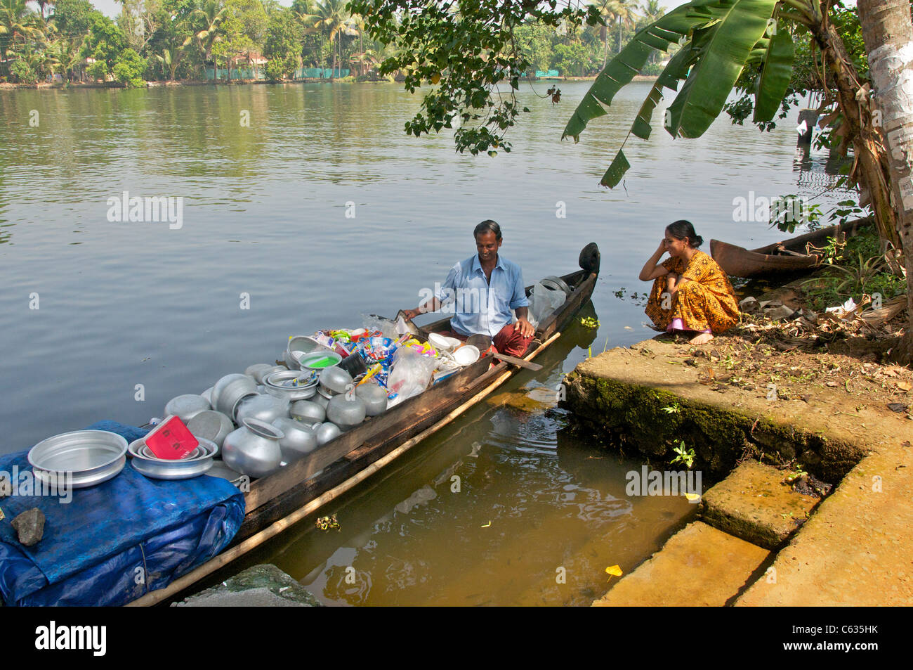 Man selling pots and pans and household goods from canoe Backwaters Kerala South India - Stock Image