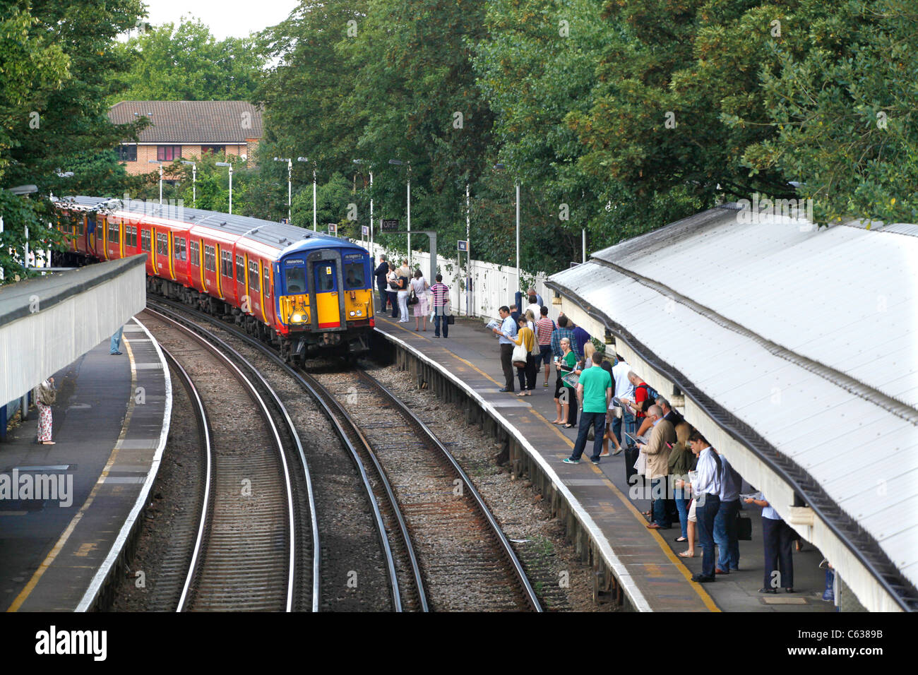 Commuters waiting for the morning train at Mortlake, London - Stock Image