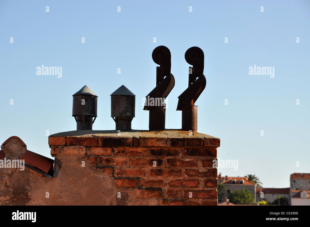 Four exhaust pipes on a brick chimney - Stock Image