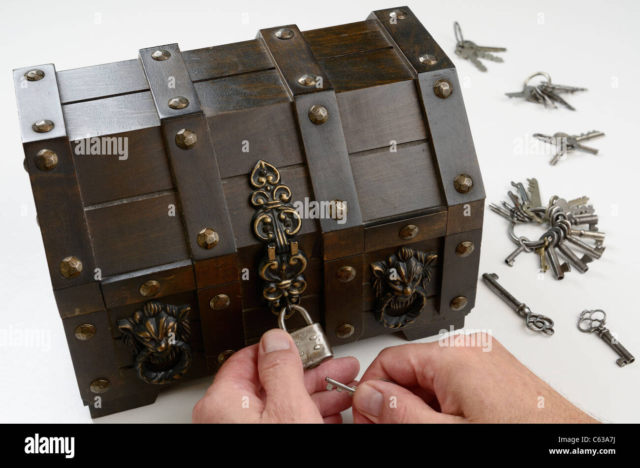 Man's hands searching for the key to fit the lock on a treasure chest - Stock Image