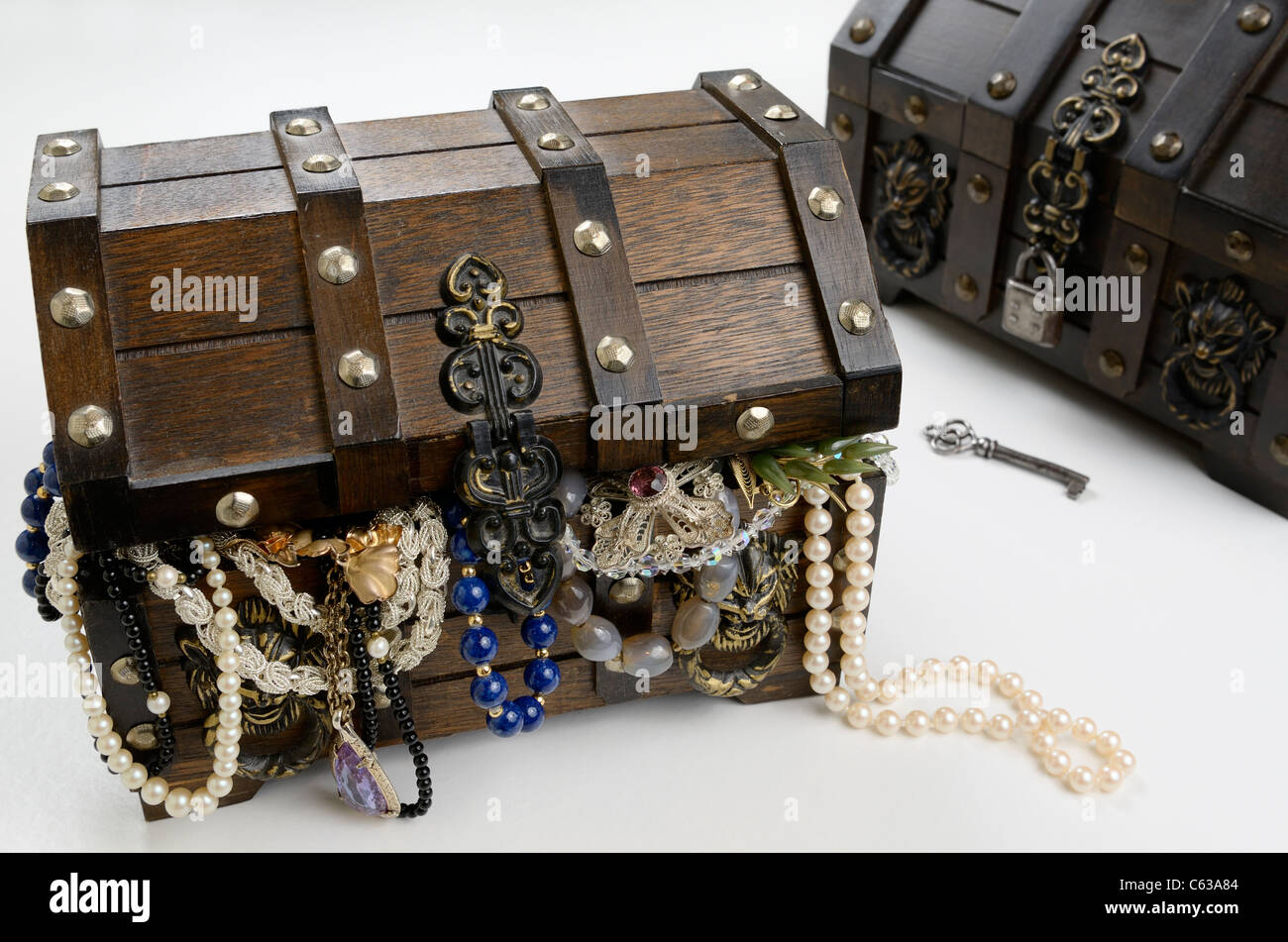 Two treasure chests one open and overflowing with riches of pearls and jewels - Stock Image
