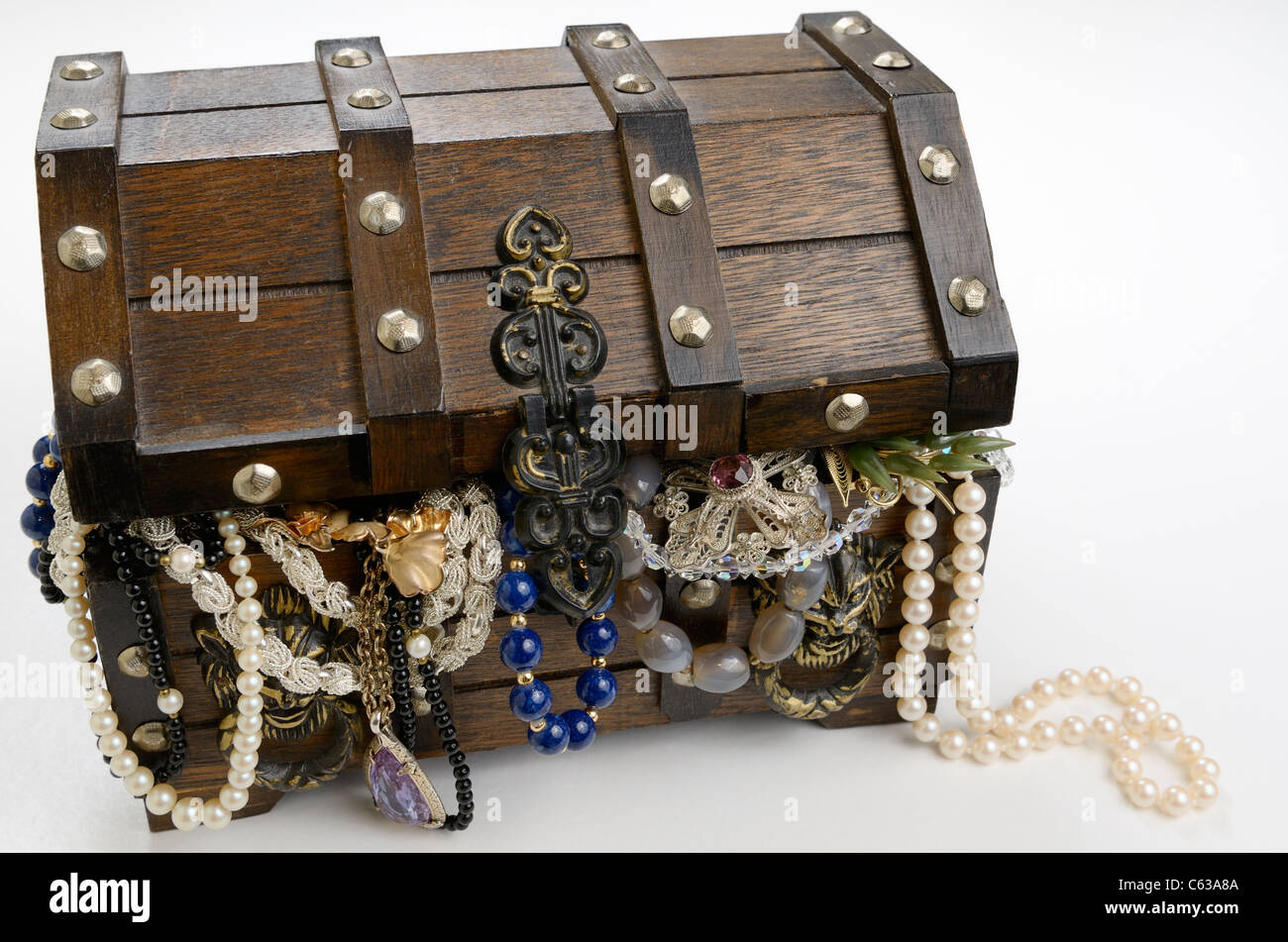 Treasure chest overflowing with riches of pearls and jewels on white background - Stock Image