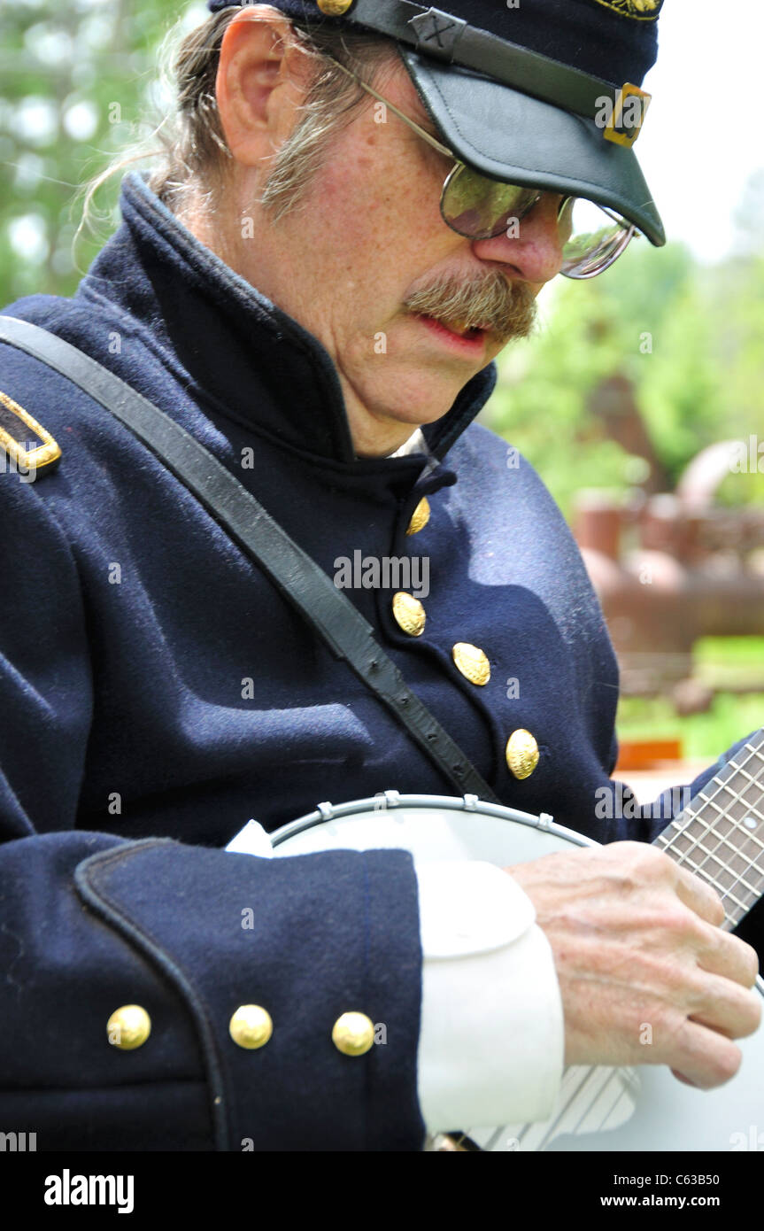 Man in Civil War era Union Army uniform playing a banjo at Pioneer Day celebration in Idaho City, Idaho - Stock Image