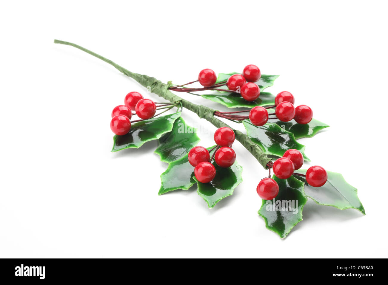Branch of holly with red berries, isolated on white background. - Stock Image