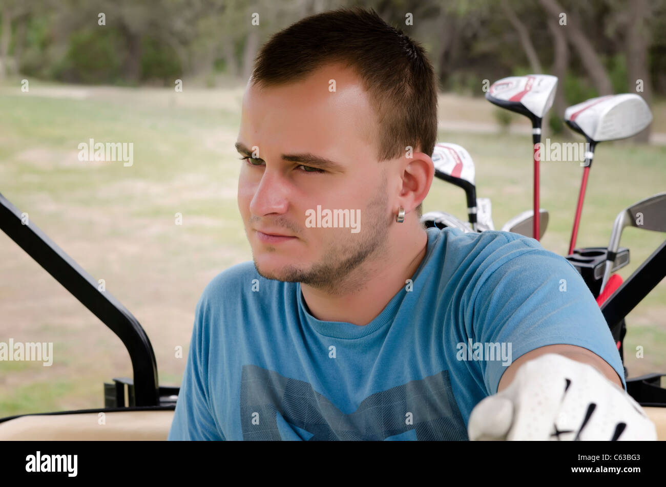 Young player riding golf cart - Stock Image